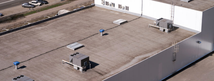 Roof of a commercial building with a external units of the commercial air conditioning and ventilation systems